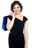 Aantrekkelijke shopaholic vrouw dragende het winkelen zak Royalty-vrije Stock Afbeeldingen
