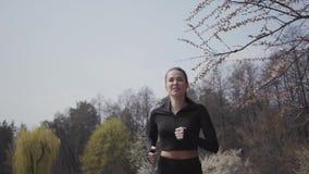 Aantrekkelijke slanke jonge vrouw in sportkleding die op riverbank lopen Actieve levensstijl, sport De dame die haar lichaam houd stock footage