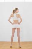 Aantrekkelijke slanke vrouw die sportkleding stellen dragen die zich in sporthal bevinden Royalty-vrije Stock Foto