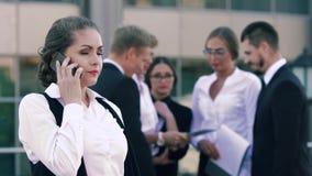 Aantrekkelijke slim-kijkt bedrijfsvrouw op de telefoon spreken en haar collega's die zich op de achtergrond bevinden en het babbe stock video