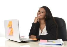 Aantrekkelijke Spaanse onderneemsterzitting bij bureau die bij computerlaptop gelukkig glimlachen werken Royalty-vrije Stock Foto's