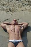 Aantrekkelijke spier jonge mens die op het strand, grote copyspace rusten Stock Foto's