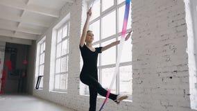 Aantrekkelijke tienerturner die met gekleurd lint in sportgymnastiek op witte achtergrond dichtbij vensters dansen aantrekkelijk stock footage