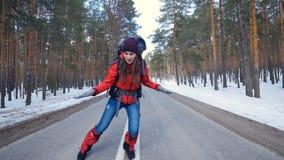 Aantrekkelijke toerist die pret hebben die op een de winterweg in bos lookung in camera dansen stock video