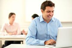 Aantrekkelijke uitvoerende kerel die aan zijn laptop werken stock foto's