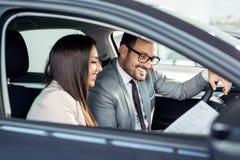 Aantrekkelijke verkoopster die binnen van een auto aan klant tonen royalty-vrije stock foto's