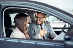 Aantrekkelijke verkoopster die binnen van een auto aan klant tonen stock foto's