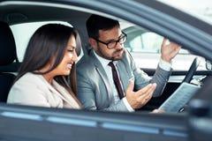 Aantrekkelijke verkoopster die binnen van een auto aan klant tonen binnen van een auto aan klantrive nieuwe auto royalty-vrije stock foto's