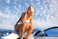 Aantrekkelijke verstoorde jonge vrouwenzitting op haar auto Royalty-vrije Stock Foto