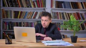 Aantrekkelijke volwassen die zakenman die door de fout wordt geërgerd worden en wordt gefrustreerd terwijl het werken aan laptop  stock video