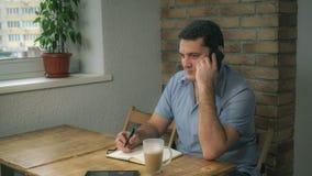 Aantrekkelijke volwassen mens die in een koffie en besprekingen op de telefoon rusten stock foto