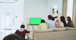 Aantrekkelijke vrienden in een grote woonkamer die op een groene het schermtv op een voetbalwedstrijd letten steunen zij hun best stock video