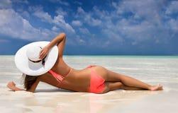 Aantrekkelijke vrouw in bikini die op een strand liggen royalty-vrije stock afbeeldingen