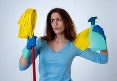 Aantrekkelijke vrouw boos en rusteloos van het schoonmaken en huishouden stock foto