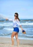 Aantrekkelijke vrouw in borrels lopen gelukkig op strandzand die s dragen stock afbeeldingen