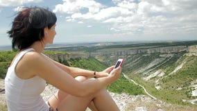 Aantrekkelijke vrouw die aan muziek met hoofdtelefoons op smartphone op een achtergrond van bergen luisteren stock videobeelden