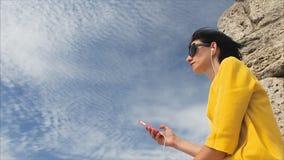 Aantrekkelijke vrouw die aan muziek met hoofdtelefoons op smartphone op een achtergrond van hemel en de ruïnes van oud luisteren stock video