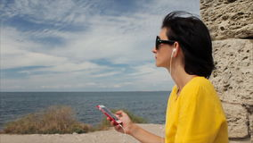 Aantrekkelijke vrouw die aan muziek met hoofdtelefoons op smartphone op een achtergrond van overzees en de ruïnes van oud luister stock videobeelden