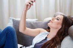 Aantrekkelijke vrouw die aangezien zij sms leest glimlachen Stock Foto