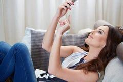 Aantrekkelijke vrouw die aangezien zij sms leest glimlachen Royalty-vrije Stock Fotografie