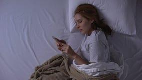 Aantrekkelijke vrouw die in bed liggen en met vriend vóór slaap babbelen stock videobeelden