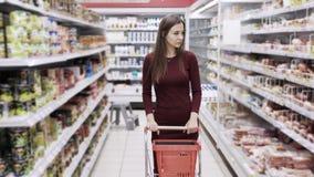 Aantrekkelijke vrouw die bij de supermarkt winkelen, steadicam schot stock video