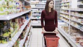 Aantrekkelijke vrouw die bij de supermarkt winkelen, steadicam schot stock footage