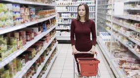Aantrekkelijke vrouw die bij supermarkt winkelen, steadicam schot stock footage