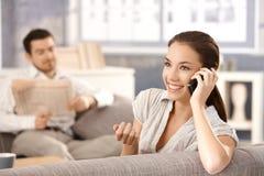 Aantrekkelijke vrouw die bij telefoon het glimlachen spreekt Royalty-vrije Stock Afbeelding