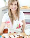 Aantrekkelijke vrouw die cakes in de keuken toont Stock Foto's