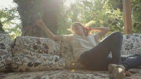 Aantrekkelijke vrouw die die en op hoofdkussens in gazebo ontspannen zitten in het bos wordt gevestigd stock video