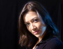 Aantrekkelijke vrouw die, donkere achtergrond glimlacht Stock Fotografie