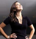 Aantrekkelijke vrouw die, donkere achtergrond glimlacht Stock Afbeeldingen