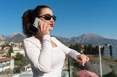 Aantrekkelijke vrouw die door mobiele telefoon op balkon met mooie mening spreken royalty-vrije stock afbeeldingen