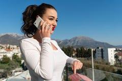 Aantrekkelijke vrouw die door mobiele telefoon op balkon met mooie mening spreken royalty-vrije stock fotografie