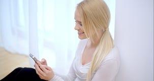 Aantrekkelijke vrouw die een bericht op haar telefoon lezen stock video