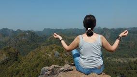 Aantrekkelijke vrouw die en bij de bovenkant van de berg ontspannen mediteren stock video