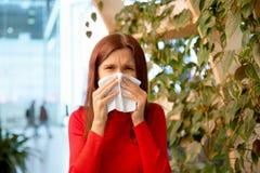 Aantrekkelijke vrouw die, die en haar neus in een zakdoek fronsen blazen het concept de lentekoude en allergieën royalty-vrije stock afbeelding