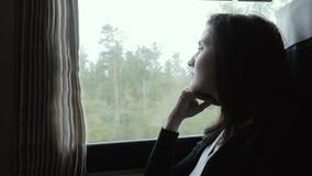 Aantrekkelijke Vrouw die in Gedachte uit een Treinvenster kijken, Langzame Motie, Reisconcept stock video