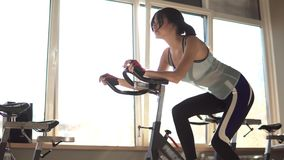 Aantrekkelijke vrouw die haar duurzaamheid verbeteren terwijl het uitwerken op een exercycle stock videobeelden