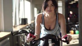 Aantrekkelijke vrouw die haar duurzaamheid verbeteren terwijl het uitwerken op een exercycle stock video
