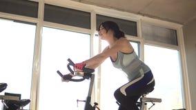 Aantrekkelijke vrouw die haar duurzaamheid verbeteren terwijl het uitwerken op een exercycle portret van een mooi meisje in de gy stock video
