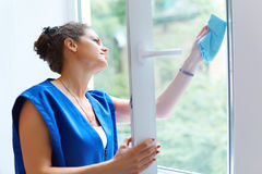 Aantrekkelijke Vrouw die het Venster wassen Schoonmakende Bedrijfarbeider wor royalty-vrije stock foto's