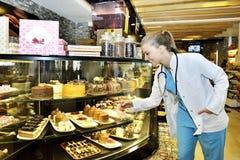 Aantrekkelijke vrouw die in koffie cake kiezen stock afbeeldingen