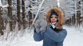 Aantrekkelijke vrouw die in matroos met bont` s kap op haar mobiele telefoon in de winterpark babbelen stock videobeelden