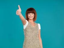 Aantrekkelijke vrouw die met haar omhoog duim glimlacht stock foto's
