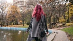 Aantrekkelijke vrouw die met rood haar rond een park met kunstmatig meer lopen Zij draait rond en glimlacht aan stock footage