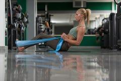 Aantrekkelijke Vrouw die met Rubber in Gymnastiek uitwerken royalty-vrije stock foto's