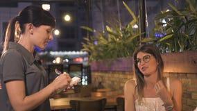 Aantrekkelijke vrouw die met serveersterzitting bij lijst in elegant restaurant spreken Serveerster die ordevoedsel in romantisch stock video