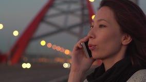 Aantrekkelijke Vrouw die Mobiele Telefoon spreken tijdens Gang op Straten van avondstad stock footage